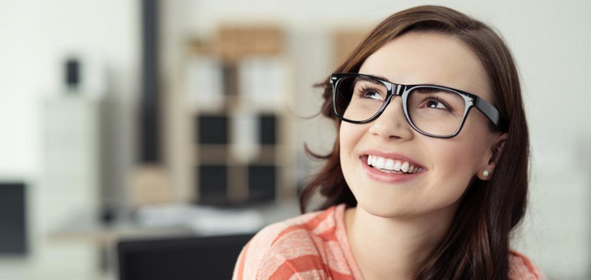 Junge Frau mit Brille blickt zufrieden und lächelnd nach oben.