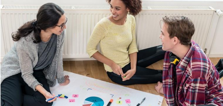 Eine Lerngruppe sitzt im Kreis auf dem Boden.